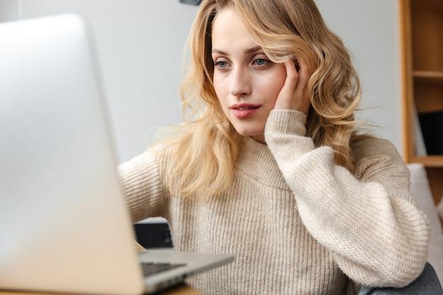 Porträt einer ziemlich ernsten jungen frau zuhause zu hause mit laptop-computer.