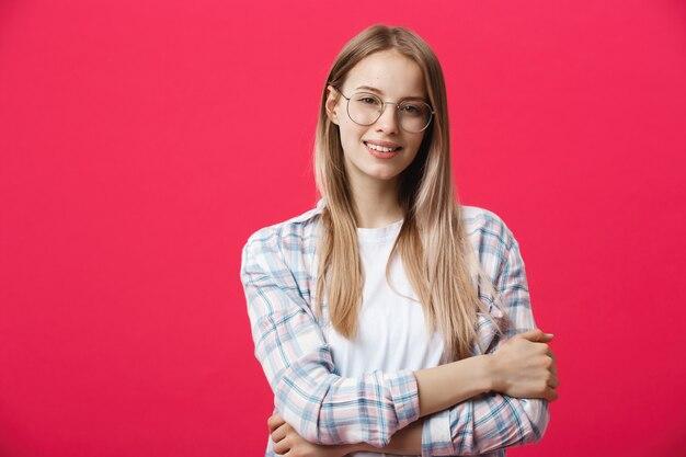 Porträt einer zufälligen frau in den gläsern, welche die kamera lokalisiert auf einem rosa hintergrund betrachten