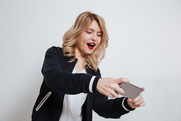 Porträt einer zufälligen jungen teenagerfrau, die auf handy spielt