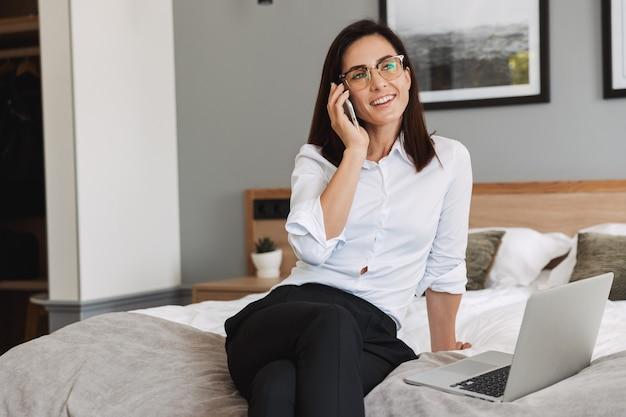 Porträt einer zufriedenen erwachsenen geschäftsfrau im formellen anzug, die auf dem smartphone spricht und einen laptop benutzt, während sie auf dem bett in der wohnung sitzt