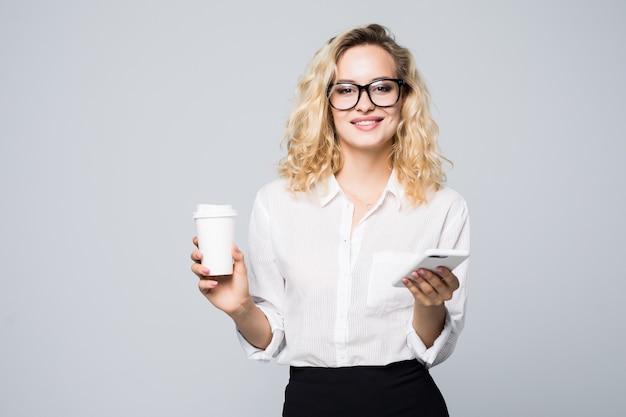 Porträt einer zufriedenen jungen geschäftsfrau, die handy während des haltens der tasse kaffee verwendet, um über weiße wand isoliert zu gehen