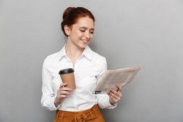 Porträt einer zufriedenen rothaarigen geschäftsfrau der 20er jahre in formeller kleidung, die kaffee zum mitnehmen trinkt und zeitung im büro isoliert über grau liest