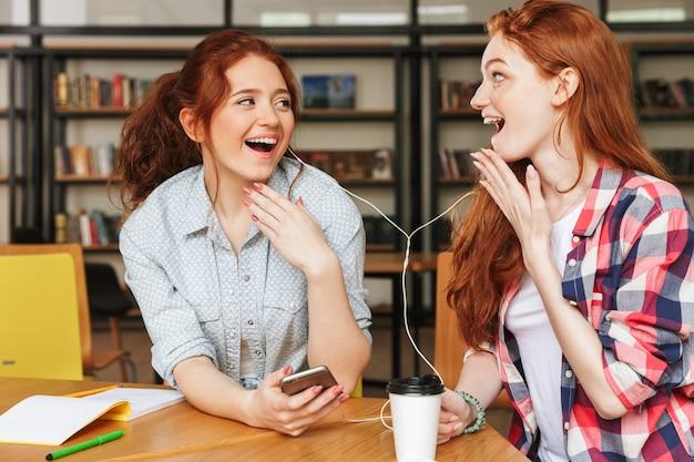 Porträt einer zwei lächelnden teenager-mädchen, die musik hören