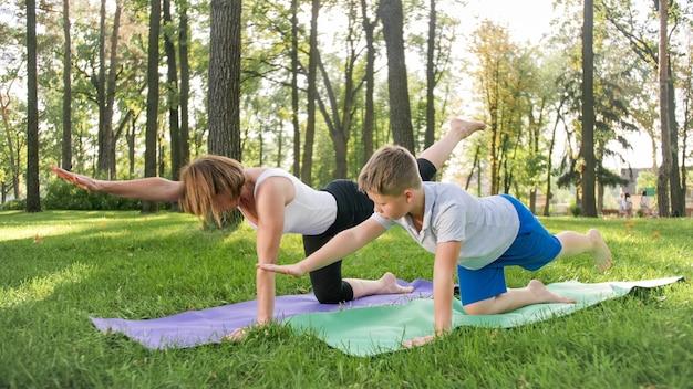 Porträt eines 12-jährigen jungen, der mit seiner mutter im park yoga-übungen macht. familie meditiert und streckt sich im wald