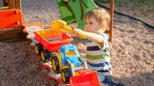 Porträt eines 3 jahre alten kleinen jungen, der im sandkasten mit spielzeug-lkw und anhänger spielt