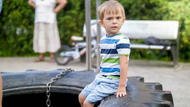Porträt eines 3 jahre alten kleinkindjungen, der auf dem großen gummireifen auf dem kinderspielplatz im park witzelt