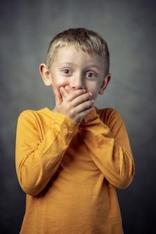 Porträt eines 6-jährigen jungen, der seinen mund mit beiden händen bedeckt.