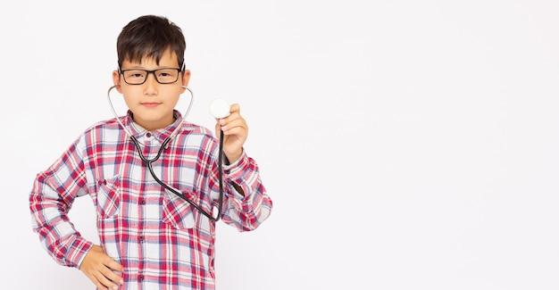 Porträt eines 8-jährigen jungen, der mit stethoskop arzt vortäuscht oder spielt.
