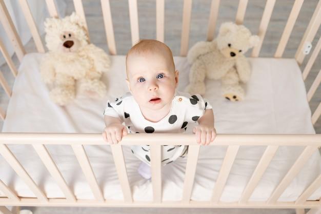 Porträt eines 8 monate alten babys, das in einem kinderbett mit spielzeug im schlafanzug in einem hellen kinderzimmer steht und in die kamera schaut