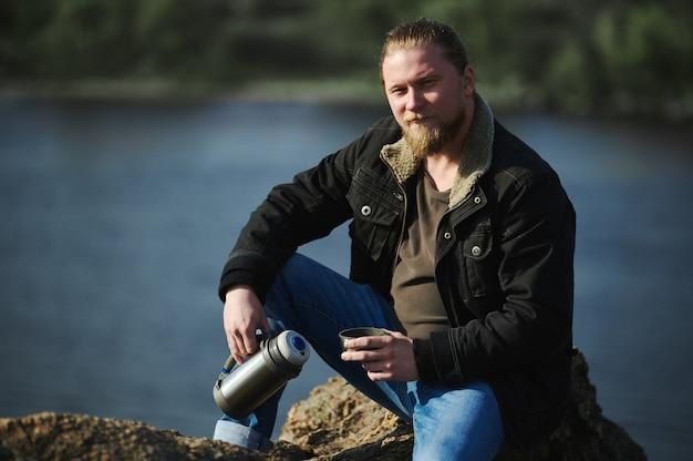 Porträt eines abenteurers, der auf felsen sitzt und thermoskanne mit heißem getränk hält und eine pause beim wandern in der natur macht.