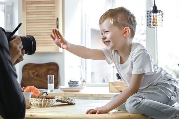 Porträt eines abwegigen jungenmodells, das vor dem fotografen posiert, der auf dem tisch in der küche sitzt