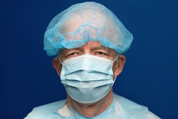 Porträt eines älteren erwachsenen, der in einer chirurgischen gesichtsmaske mit ohrriemen gekleidet ist und nase und mund von sars bedeckt, virulent infektiöses corona-virus. mann in medizinischer kleidung auf klassischem blauem hintergrund