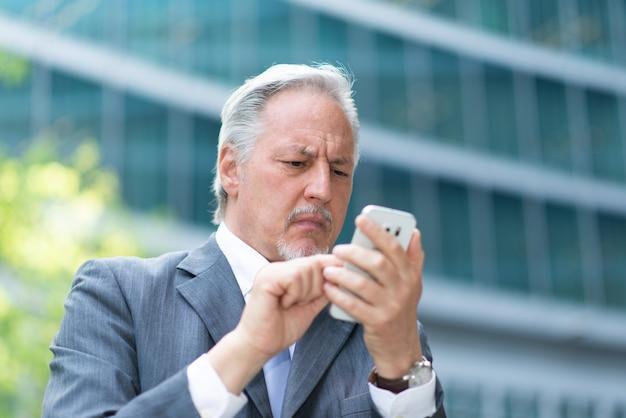 Porträt eines älteren geschäftsmannes, der eine schwierige zeit hat, während er sein handy benutzt