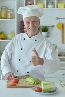 Porträt eines älteren männlichen kochs, der salat kocht