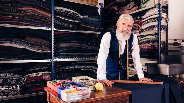Porträt eines älteren männlichen modedesigners in seinem shop, der kamera betrachtet