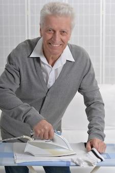 Porträt eines älteren mannes beim bügeln