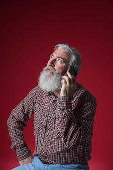 Porträt eines älteren mannes, der am handy oben schaut gegen roten hintergrund spricht