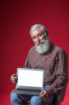 Porträt eines älteren mannes, der auf dem stuhl zeigt laptop mit leerem weißem schirm gegen roten hintergrund sitzt