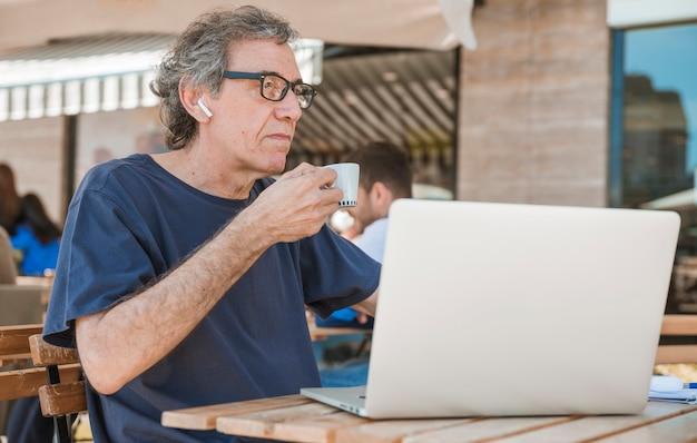 Porträt eines älteren mannes, der die kaffeetasse sitzt am café im freien mit laptop hält