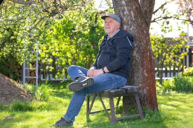 Porträt eines älteren mannes, der draußen auf einer bank im park sitzt optimismus guter gesundheitsausdruck ruhestand oder rentenkonzept pension