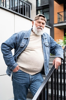 Porträt eines älteren mannes, der draußen in der stadt auf treppen posiert