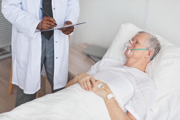 Porträt eines älteren mannes, der im krankenhausbett mit sauerstoffergänzungsmaske liegt und afroamerikanischen arzt ansieht, kopierraum