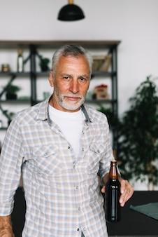 Porträt eines älteren mannes, der in der hand bierflasche hält