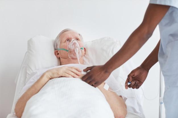 Porträt eines älteren mannes, der mit sauerstoffmaske im krankenhausbett liegt und eine männliche krankenschwester betrachtet, die iv-tropf einstellt, kopienraum