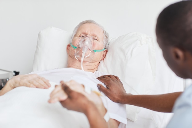 Porträt eines älteren mannes, der mit sauerstoffmaske im krankenhausbett liegt und händchen mit einem fürsorglichen arzt oder einer krankenschwester hält