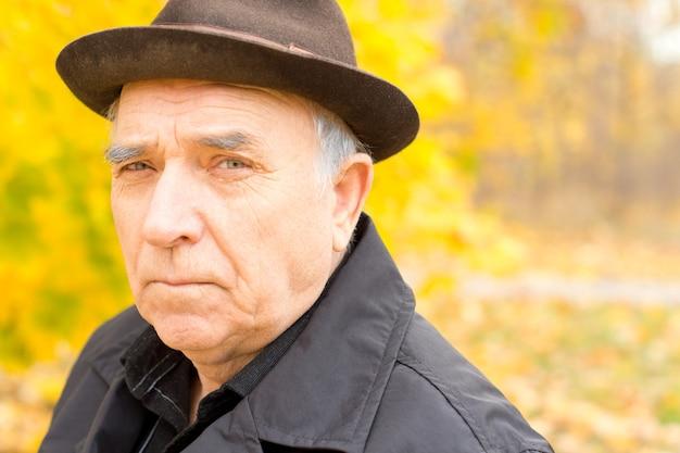 Porträt eines älteren mannes in einem warmen hut und mantel draußen in einem bunten gelben wald