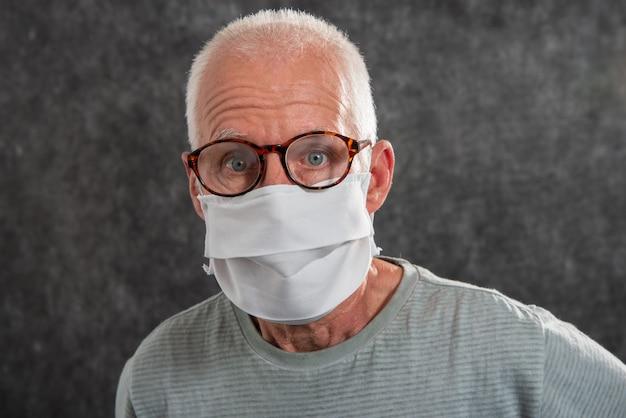 Porträt eines älteren mannes in einer medizinischen maske