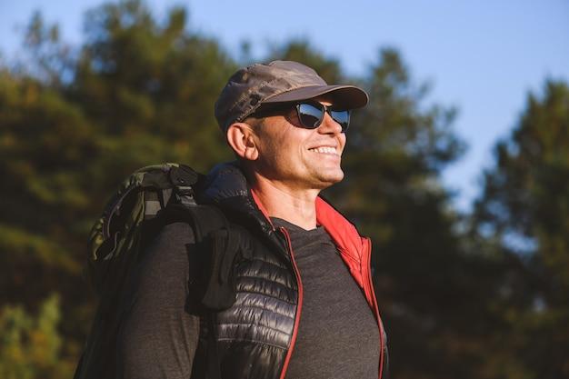 Porträt eines älteren mannes mit rucksack auf waldhintergrund