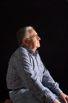 Porträt eines älteren mannes mit schwarzem hintergrund