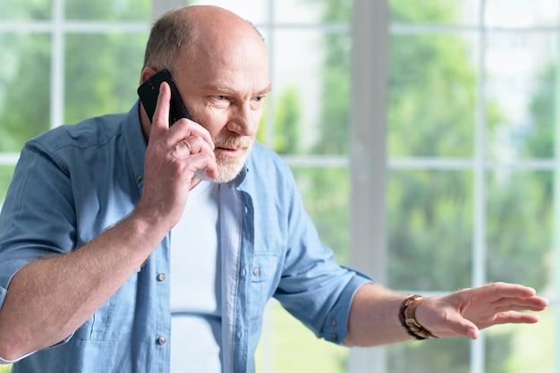 Porträt eines älteren mannes mit telefon zu hause