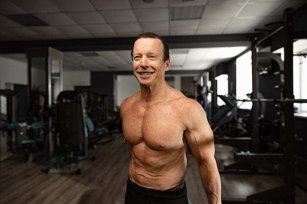 Porträt eines älteren muskulösen mannes in einem fitnessstudio