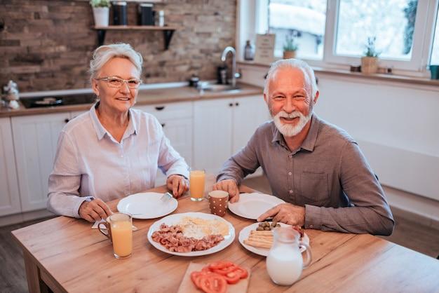 Porträt eines älteren paares, das bei tisch sitzt, frühstückend zu hause und betrachten kamera.
