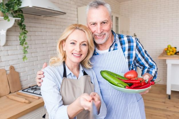 Porträt eines älteren paares, das in der küche nimmt selfie am handy steht