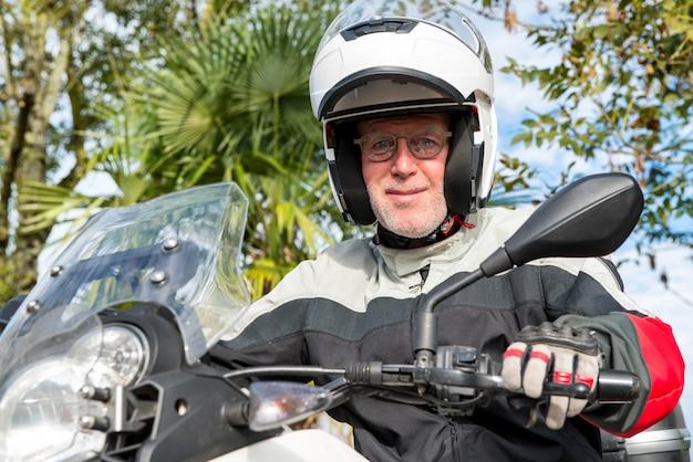 Porträt eines älteren radfahrers auf seinem motorrad