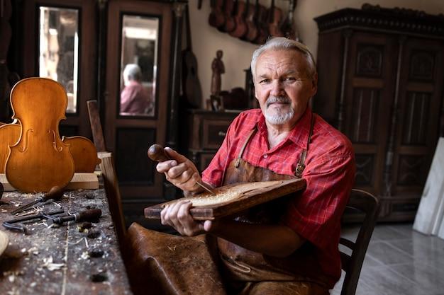 Porträt eines älteren tischlers, der werkzeuge und holz in seiner altmodischen werkstatt hält