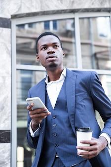 Porträt eines afrikanischen jungen geschäftsmannes in der blauen klage, die mitnehmerkaffeetasse unter verwendung des handys hält