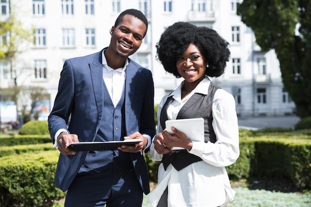 Porträt eines afrikanischen jungen geschäftsmannes und der geschäftsfrau, die das klemmbrett und digitale tablette betrachten kamera hält