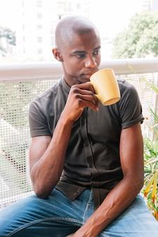 Porträt eines afrikanischen jungen mannes, der den kaffee im balkon trinkt