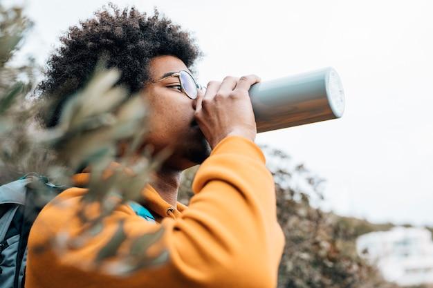 Porträt eines afrikanischen mannes, der das wasser trinkt