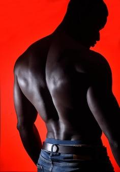 Porträt eines afrikanischen mannes hemdlos auf rotem hintergrund
