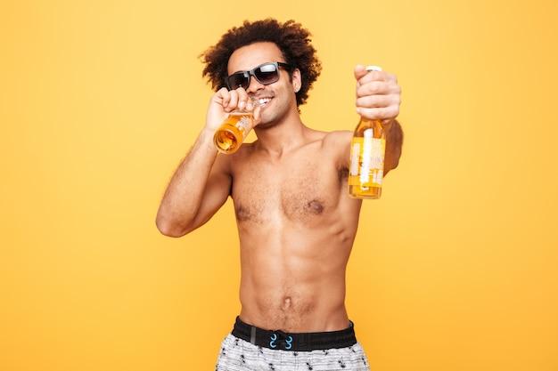 Porträt eines afrikanischen mannes in der sonnenbrille, die bierflasche zeigt