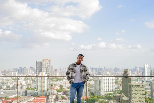 Porträt eines afrikanischen schwarzen mannes im freien in der stadt auf dem dach während der horizontalen aufnahme im sommer
