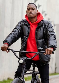 Porträt eines afroamerikaners und seines fahrrads