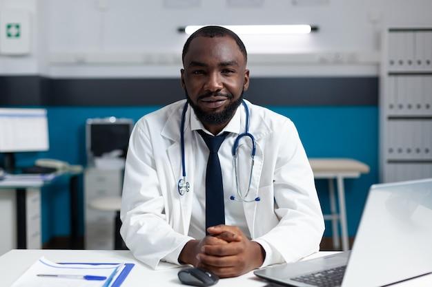 Porträt eines afroamerikanischen arztes, der im krankenhausbüro arbeitet