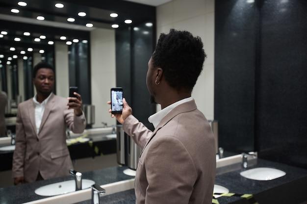 Porträt eines afroamerikanischen geschäftsmannes, der spiegel-selfie in der öffentlichen toilette macht, platz kopieren