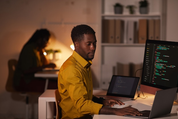 Porträt eines afroamerikanischen it-entwicklers, der code auf mehreren computerbildschirmen schreibt, während er spät im büro arbeitet, kopiert speicherplatz